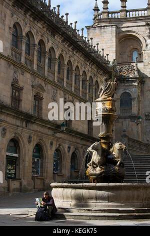 Pilgrim on St James pilgrimage by Dos Cavalos horse fountain Praza das Praterias, Santiago de Compostela, Galicia, - Stock Photo