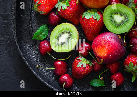 Summer juicy ripe Strawberry, cherry, kiwi and peaches On a black plate closeup. - Stock Photo
