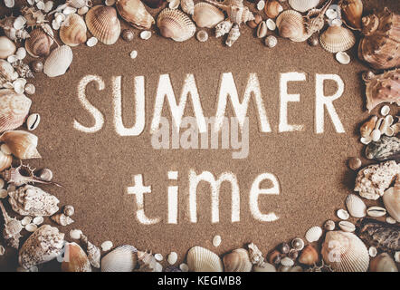 Summer time is written on the sand in frame of sea shells. Travel, summer, relax concept. Toned - Stock Photo