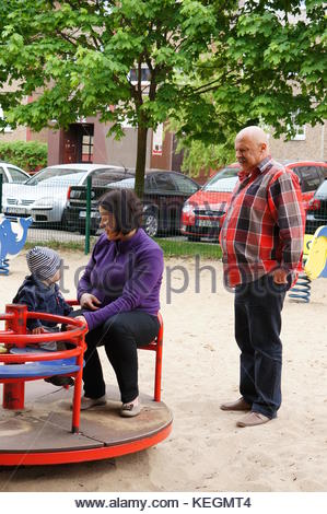 POZNAN, POLAND - MAY 16, 2015: Woman sitting with child on roundabout next to senior man at a play ground - Stock Photo
