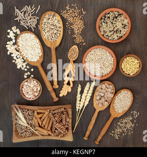 High fiber health food of whole wheat pasta, cereal and grains in bowls and spoons on rustic oak background. - Stock Photo