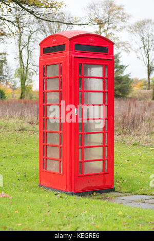 Old Red Telephone Box Single In Isolation On Green Grass Rural - Stock Photo