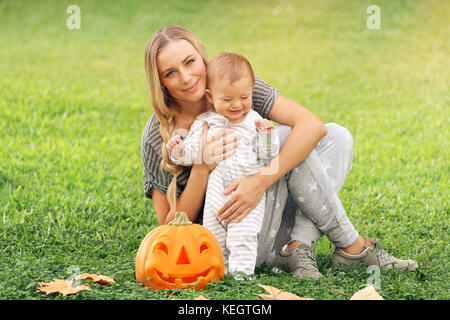 Happy mother with little baby outdoors, sitting on green grass field with orange carved pumpkin, preparation to - Stock Photo