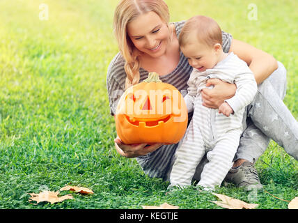 Happy mother with little baby outdoors, sitting on the green grass field and playing with orange carved pumpkin - Stock Photo