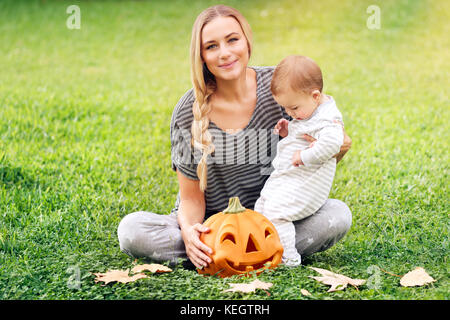 Happy family celebrating Halloween outdoors, mother with cute little baby boy playing with carved pumpkin on the - Stock Photo