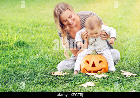 Happy young mother with her precious little son playing outdoors, cheerful baby sitting on the pumpkin with carved - Stock Photo