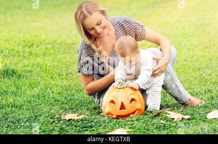 Beautiful young mother with adorable little child, playing with carved pumpkin, enjoying traditional autumn holiday, - Stock Photo