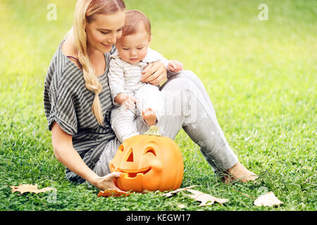 Happy mother and little baby boy outdoors, sitting on green grass field with orange carved pumpkin decorative toy, - Stock Photo