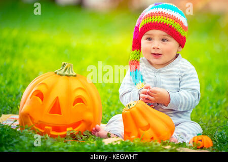Happy baby boy on Halloween holiday outdoors, sitting on green grass backyard, wearing funny festive colorful hat, - Stock Photo
