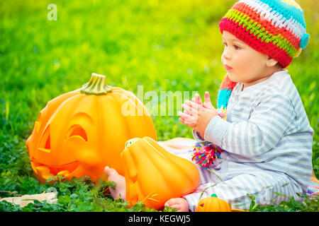 Cute little kid sitting on green grass field wearing funny colorful hat and playing with pumpkins with smiling carved - Stock Photo