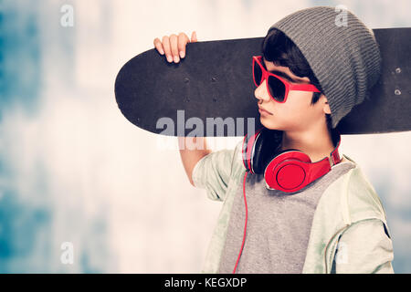 Portrait of a stylish teen boy wearing sunglasses and hat holding in hand skateboard over grunge background, modern - Stock Photo