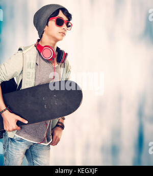 Stylish guy with skateboard over grunge background, teenager enjoying sport and music, photo with a copy space, - Stock Photo