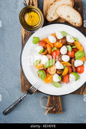 Italian Caprese salad with cherry tomatoes, small mozzarella and fresh basil in white enamel plate on rustic wooden - Stock Photo