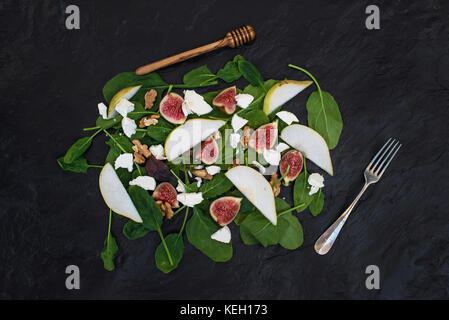 Salad with pears, baby spinach, figs, walnuts, goat cheese and honey on black stone background, top view - Stock Photo