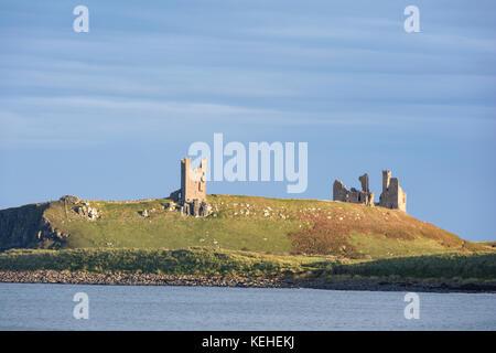 Evening light over Dunstanburgh Castle, Northumberland, England, UK - Stock Photo