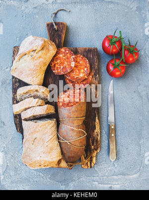 Wine snack set. Hungarian mangalica pork salami sausage, rustic bread and fresh tomatoes on dark wooden board over - Stock Photo
