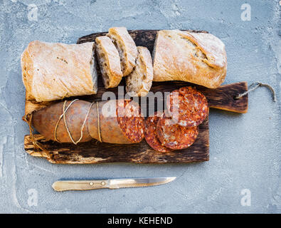 Wine snack set. Hungarian mangalica pork salami sausage and rustic bread on dark wooden board over a rough grey - Stock Photo