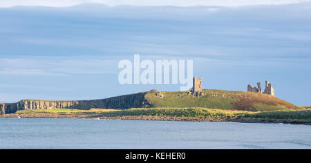 Evening light over Dunstanburgh Castle, Northumberland, England, UK - Stock Photo