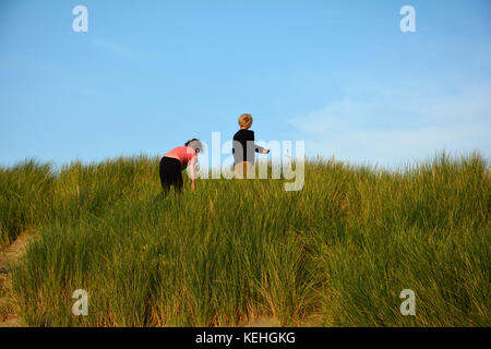 Two children on top on a sandy dune, in the middle of the beach oat on the North Sea coast - Stock Photo