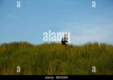 Small boy on top on a sandy dune, in the middle of the beach oat on the North Sea coast - Stock Photo