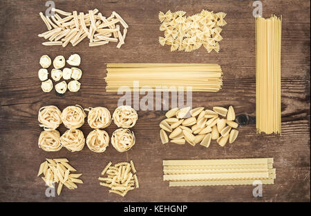 Different types of Italian uncooked pasta on rustic wooden table background, top view, horizontal - Stock Photo