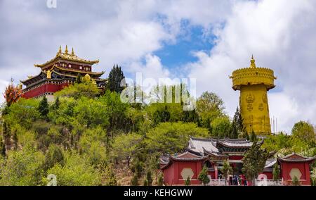 Giant tibetan prayer wheel and Zhongdian temple - Yunnan privince, China - Stock Photo