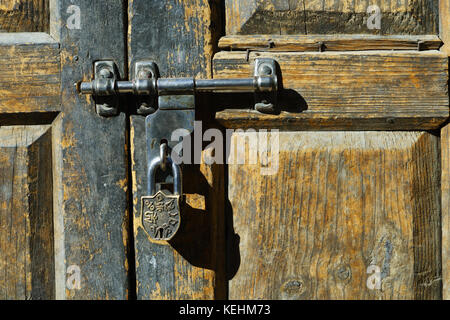 Padlock on an old weathered wooden door in Nepal. - Stock Photo