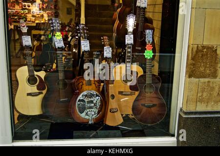 Guitars on sale in shop window, Royal Arcade, Worthing, UK - Stock Photo