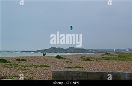 Man flying kite by the sea, Littlehampton UK - Stock Photo