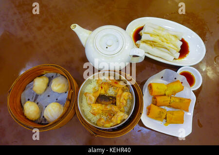 Assorted Chinese food set, dumplings, and rice noodle rolls, famous Chinese cuisine dishes on a wooden table, top - Stock Photo