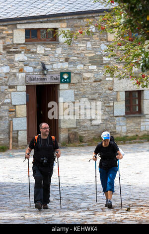 Pilgrims setting off from Habitaciones Frade to continue the Camino de Santiago pilgrim route at Triacastela in - Stock Photo