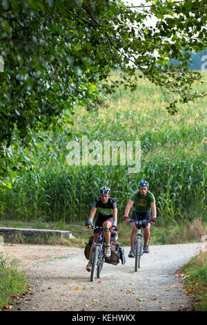 Cyclists on the Camino de Santiago Pilgrim's route to Santiago de Compostela in Galicia, Spain - Stock Photo