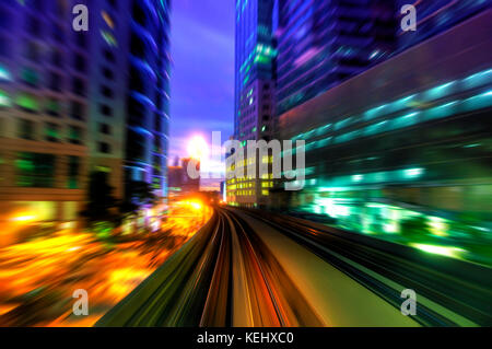 High speed train passing in between Kuala Lumpur City during dusk hour. - Stock Photo