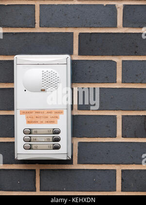 close up of metal door buzzer for apartments on wall outside; essex; england; uk - Stock Photo