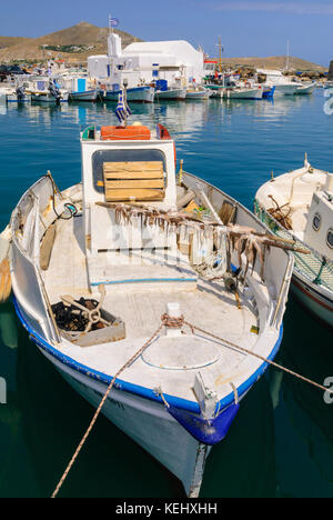 A small fishing boat with octopuses hanging out to dry in the port of Naoussa, Paros, Cyclades, Greece - Stock Photo