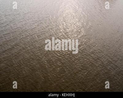 grey light streaked reflecting sea surface water background; essex; england; uk - Stock Photo