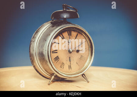 vintage alarm clock on wooden table blue background grainy stock photo