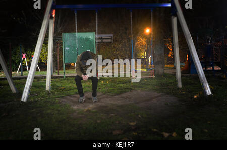 single man with a bowed head on a swing in a park outside at night in the city, concept of loneliness - Stock Photo
