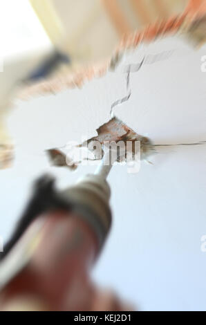 Construction worker using pneumatic hammer, construction site concept. - Stock Photo
