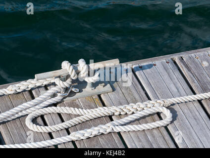 A shot of some rope tied around a mooring at the marina. - Stock Photo