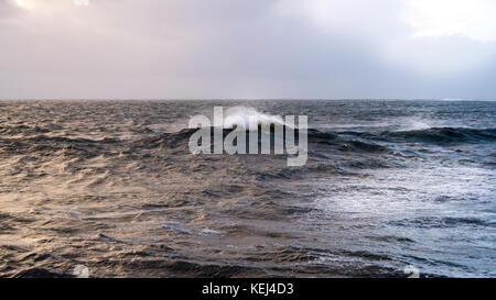 Sunlight breaking through the heavy clouds. Dramatic coastal view in the early morning as Atlantic Storm Brian reaches - Stock Photo