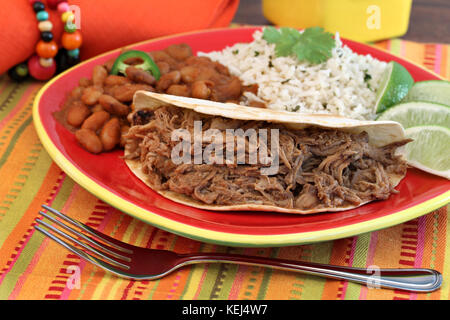 Pulled pork taco with a side of chili beans, basmati rice, and lime slices.  Selective focus on meat. - Stock Photo