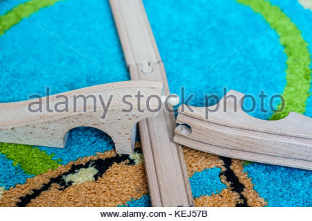 Wooden toy train track on a carpet in soft focus - Stock Photo