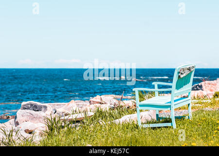 One peaceful blue aquamarine turquoise green beach chair empty bench in front of ocean - Stock Photo