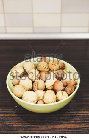 Whole hazelnuts and walnuts in a green bowl on wooden table in soft focus - Stock Photo