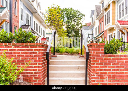 Row of colorful, red, yellow, blue, white, green painted residential townhouses, homes, houses with brick patio - Stock Photo