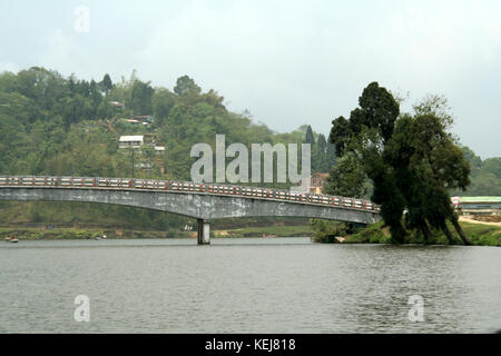 Curved bridge connecting opposite banks of lake - Stock Photo