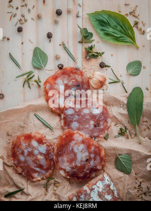 Sliced sausage salami with herbs and spices ,thyme, rosemary, saffron,basil, pepper, and oregano on the wooden table - Stock Photo
