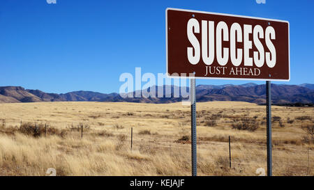 Success Just Ahead brown road sign with blue sky and wilderness - Stock Photo