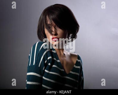 Beautiful enjoing woman moving and shaking her short black hair style with red lipstick on grey background in fashion - Stock Photo